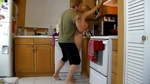 Son helps his mommy in the kitchen